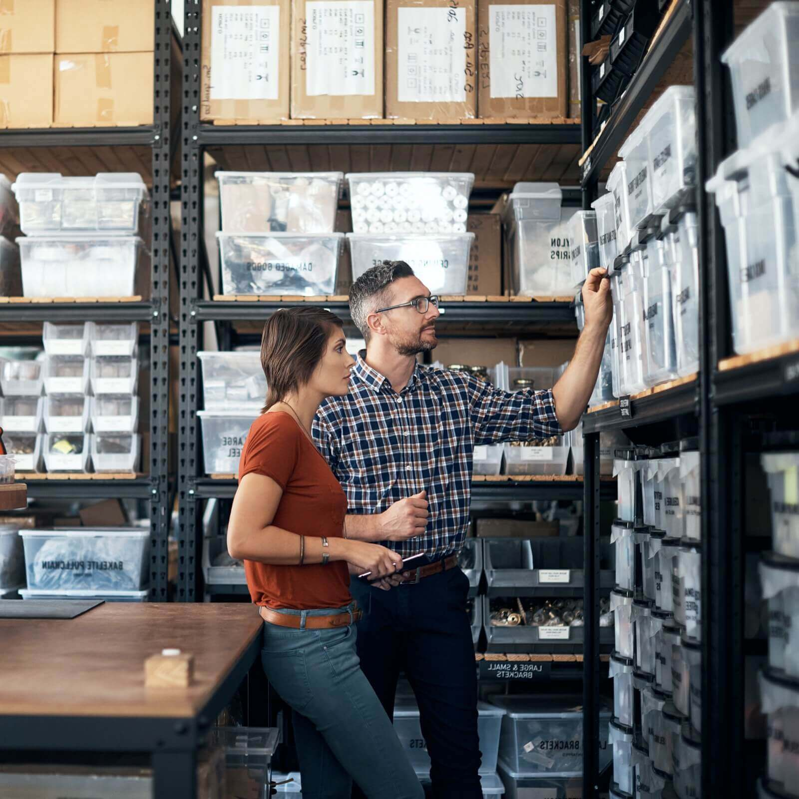 man and woman in stock room looking at items on shelf